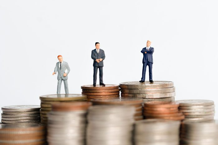Mini figure people : Small businessman standing on step or stack coins with blurred background for financial concept