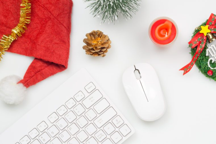 Flat lay top view Christmas office table desk party concept, Christmas workspace with keyboard, Santa Claus hat and Christmas decorations on white background