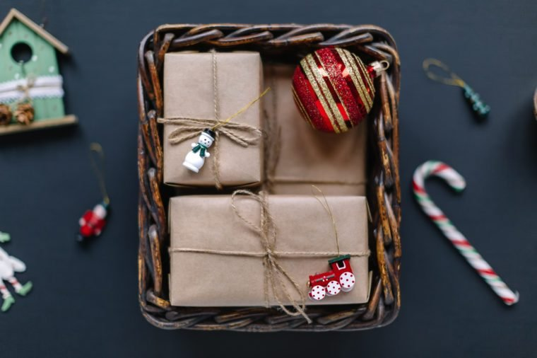 Close up flat lay photo of Christmas presents and fir toys in wooden basket. Gift boxes wrapped in kraft paper, red ball. Holiday mood. Happy New Year decoration. Merry Christmas concept.