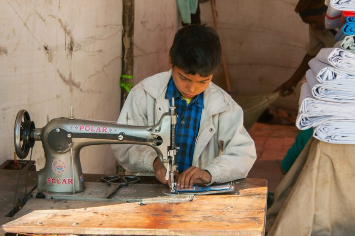 NAGAUR, INDIA - CIRCA FEBRUARY 2011: Child labor, boy sewing in booth on the market.
