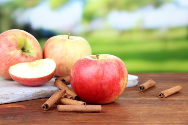 Ripe apples with cinnamon sticks on wooden table, on bright background
