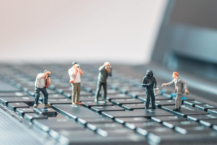miniature people robbing a business man macro photo on laptop keyboard
