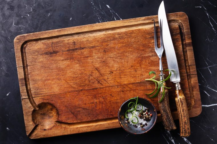 Chopping cutting board, seasonings and rosemary with fork and knife carving set on dark marble background