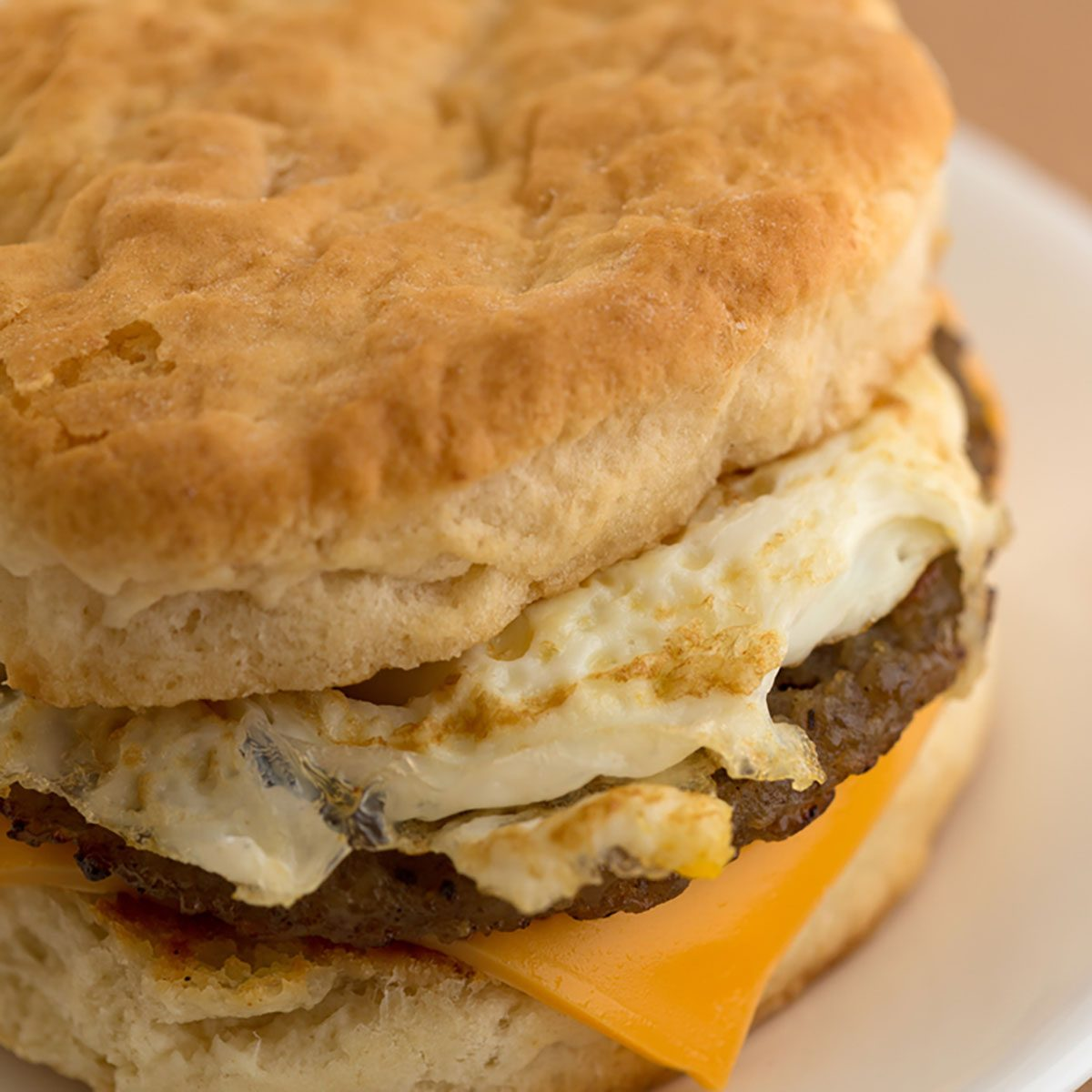 Close view of a sausage egg and cheese biscuit breakfast sandwich on a white plate upon a tan table cloth