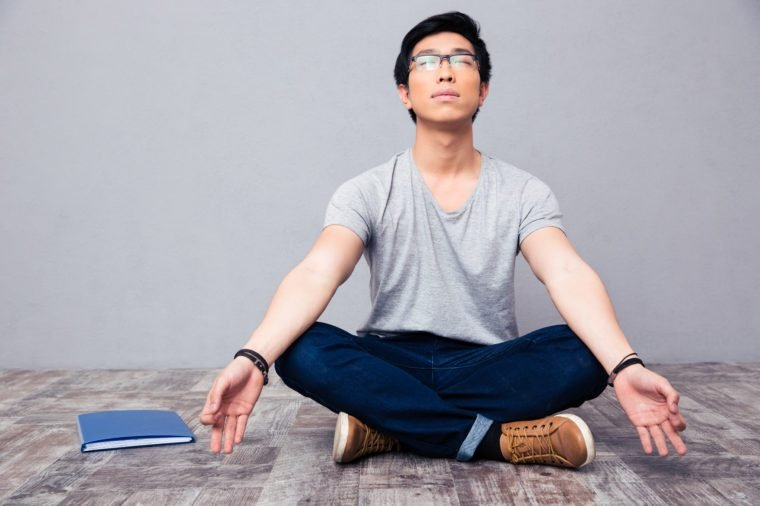Young asian man sitting on the floor and meditating