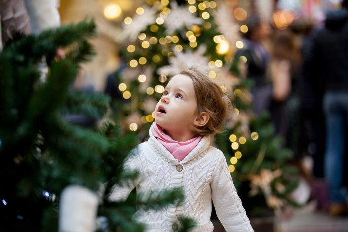 Excited little girl with open mouth looking at the beautifully decorated christmas trees with lights in the shopping mall