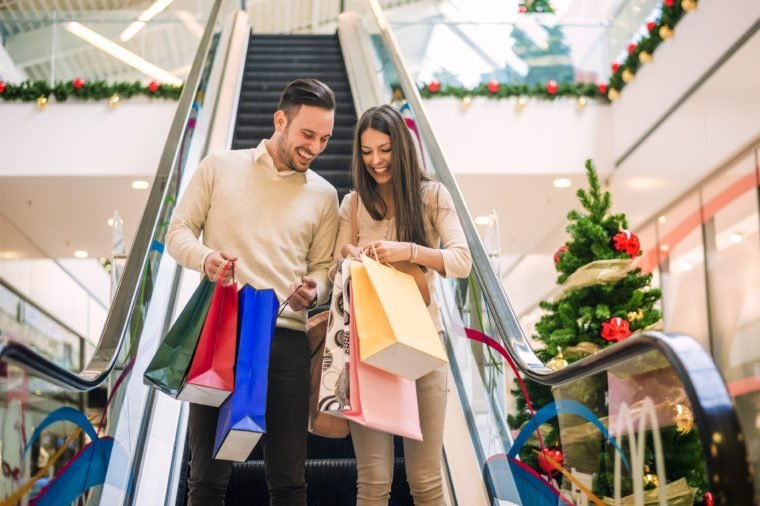 Romantic Christmas shopping.Sale, technology and people concept - happy young couple with shopping bags.Image taken inside a shopping mall.Selective focus