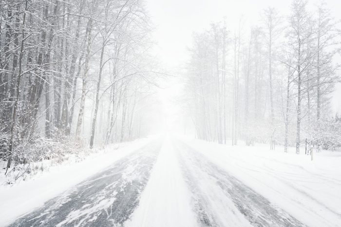 Snowy winter road during blizzard in Latvia. Heavy snow storm.