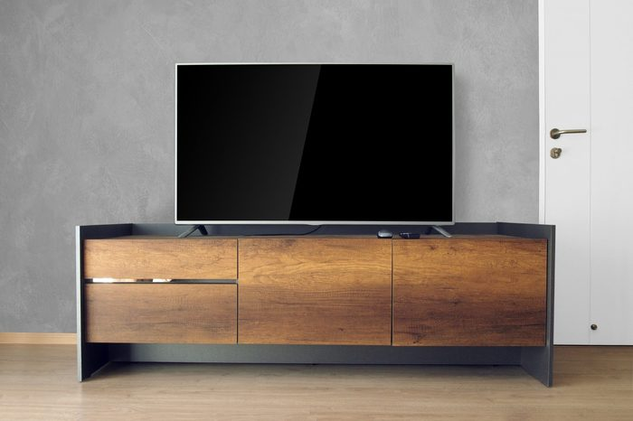 Led TV on TV stand in empty room with concrete wall. decorate in loft style.