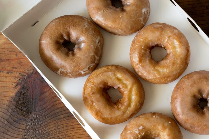 Overhead shot of six plain donuts in a white bakery box. Wood table background.