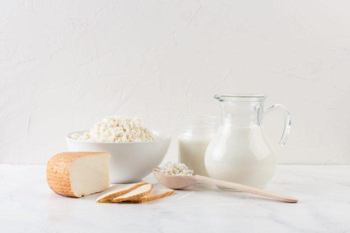 fresh dairy homemade products - cottage cheese, goat cheese, organic yogurt and milk on white background