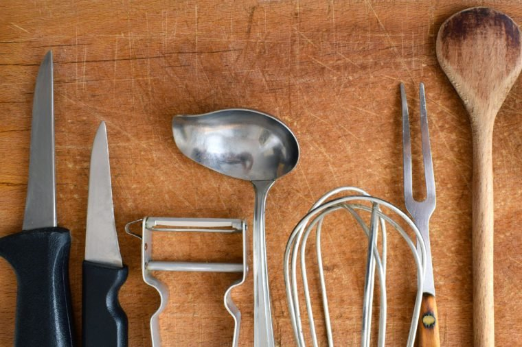 Old kitchenware lined up on a wooden cutting board, cooking tools, old cutlery, worn outdated household items