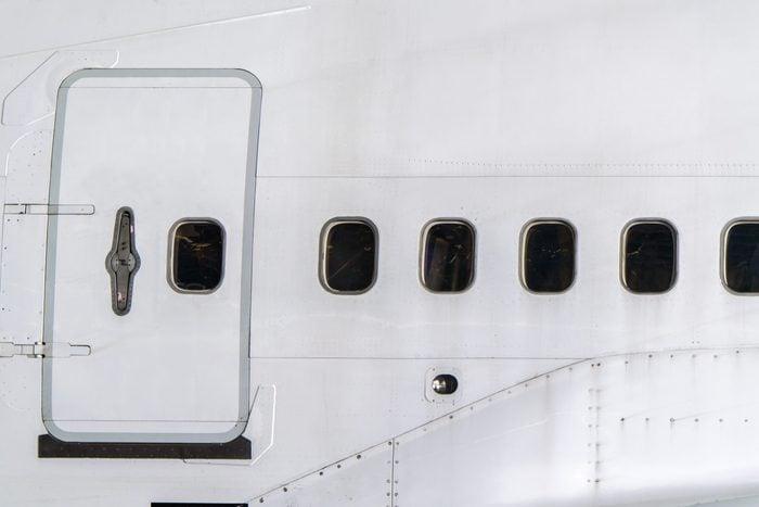 Windows of airplane with emergency exit door.