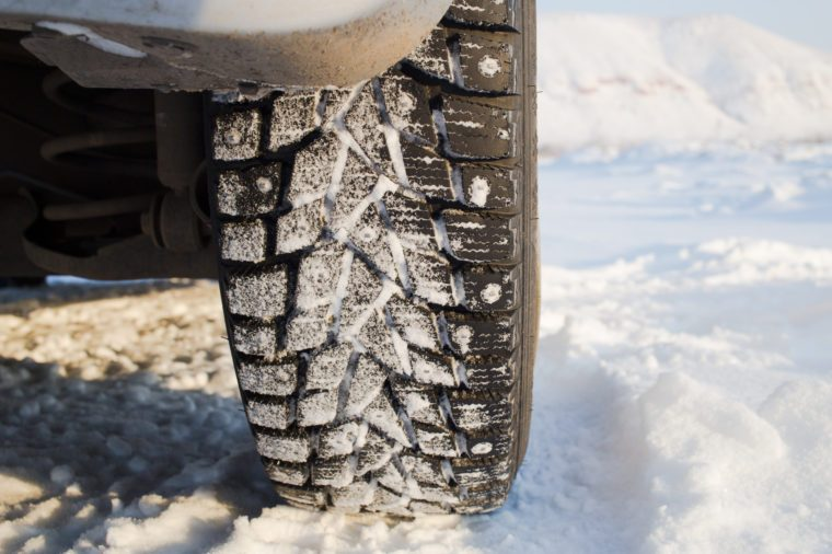 Winter studded tire on the snow .