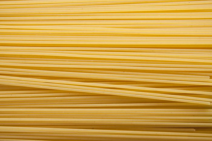 Yellow long spaghetti on black background. Thin pasta arranged in rows. Yellow italian pasta. Long spaghetti. Raw spaghetti wallpaper. Thin spaghetti. Food background concept.