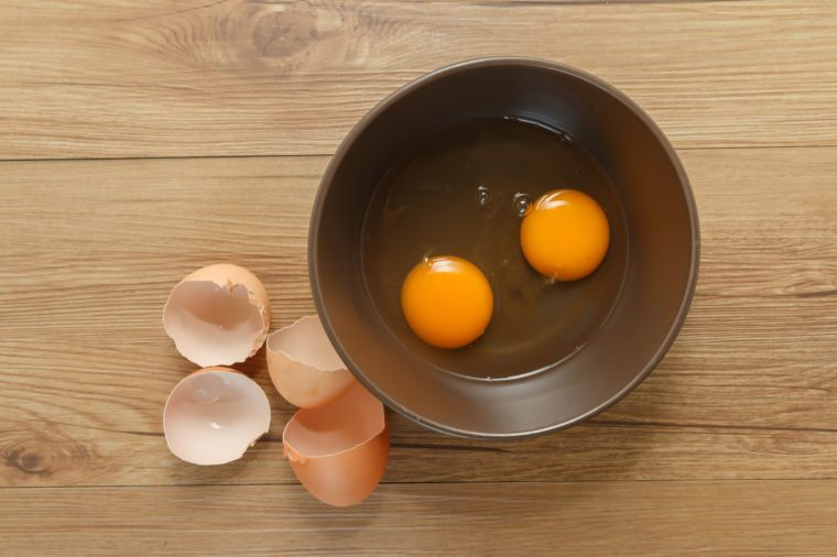 Cracked eggs in bowl and egg shells on wooden table.