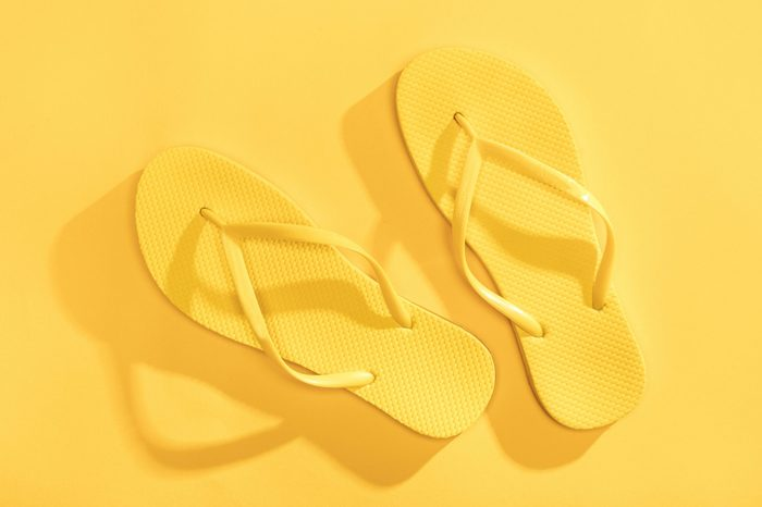Close-up top view of comfortable yellow flip-flops isolated on yellow