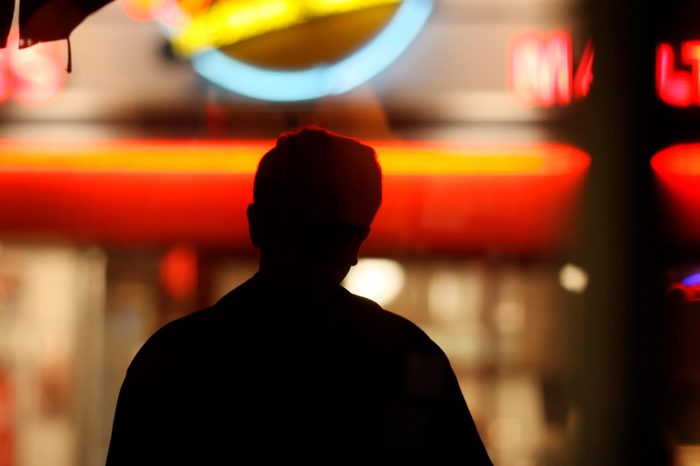 Black male silhouette over blurred neon lights background in night city
