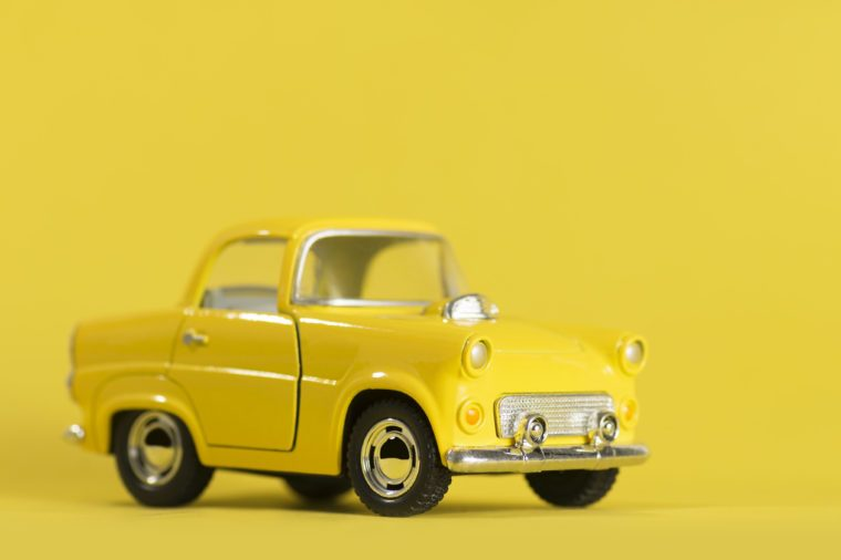 Yellow toy car on a yellow background.