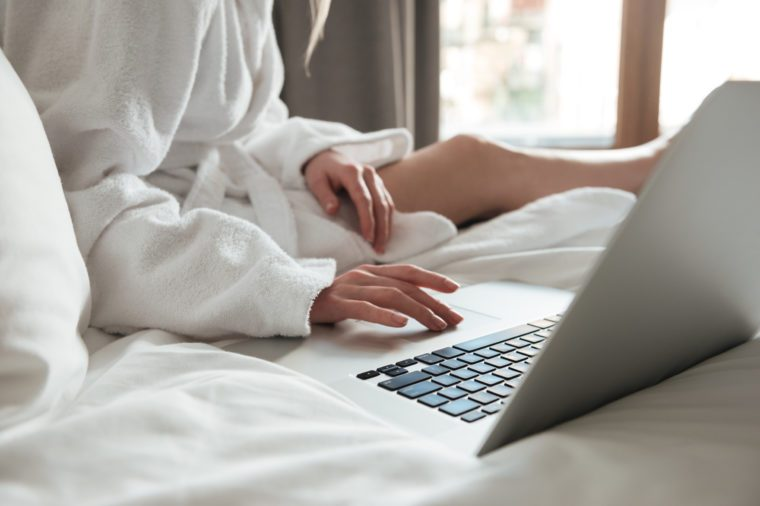 Cropped image of a woman in bathrobe on bed and using laptop in a hotel room