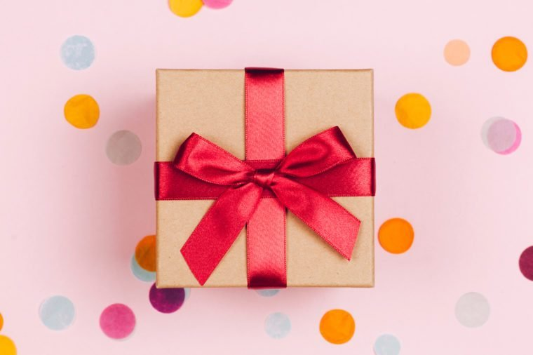Present box with red bow on pastel pink background with multicolored confetti. Flat lay style.
