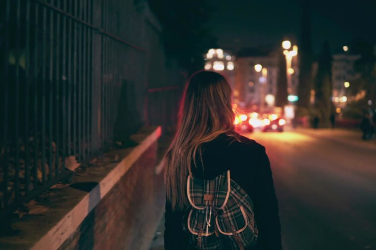Back view of brunette woman walking near the road at the traffic time. Girl goes through the city late at night alone.