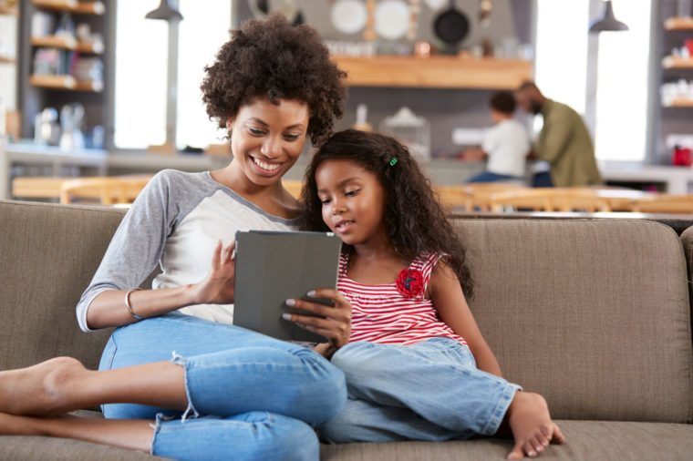 Mother And Daughter Sit On Sofa In Lounge Using Digital Tablet