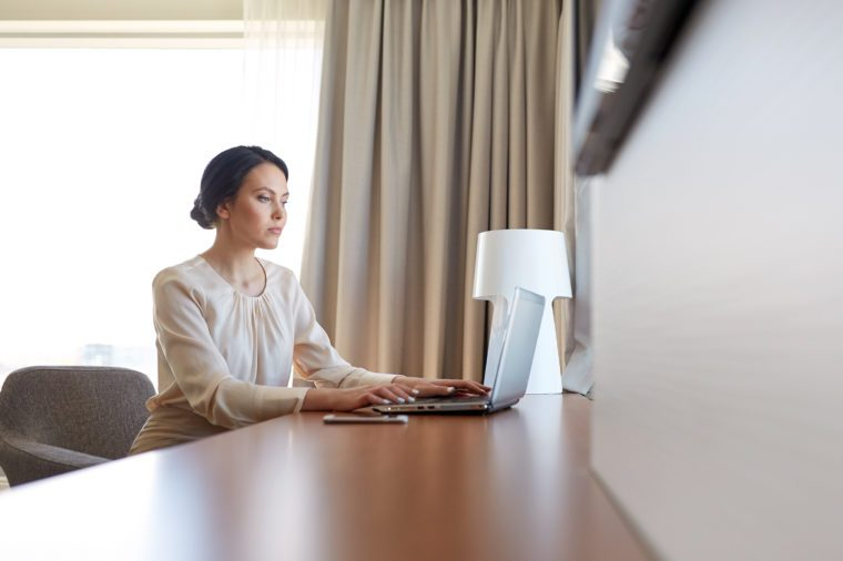 business, people and technology concept - businesswoman typing on laptop at hotel room