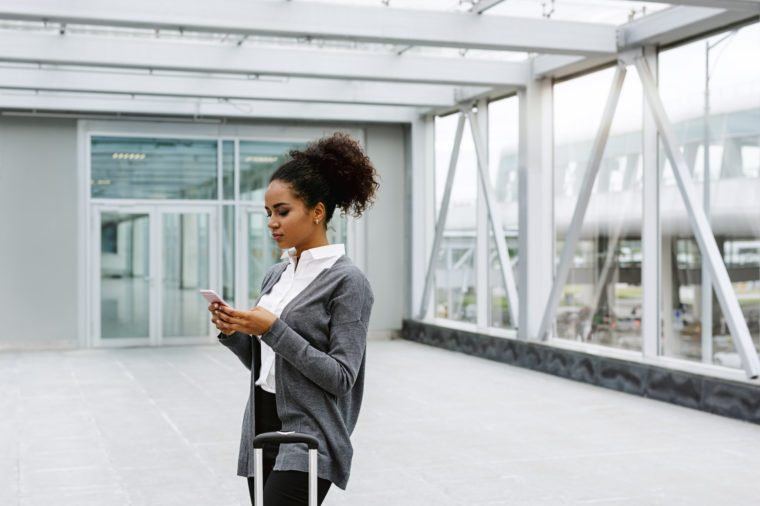 Young businesswoman waiting in airport terminal, checking mobile phone