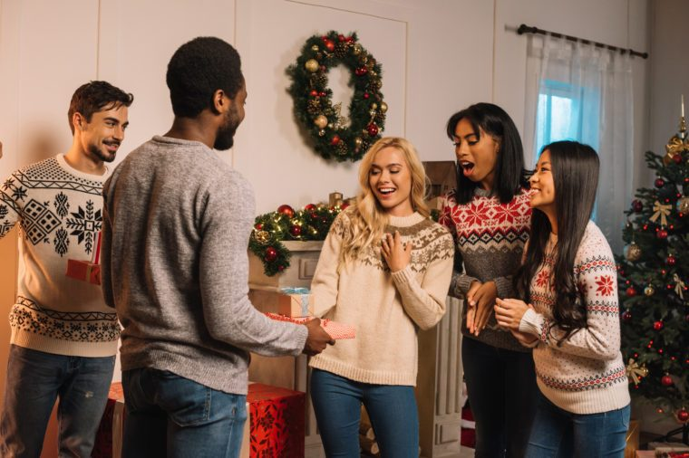 multicultural men presenting christmas gifts to friends while celebrating gifts together