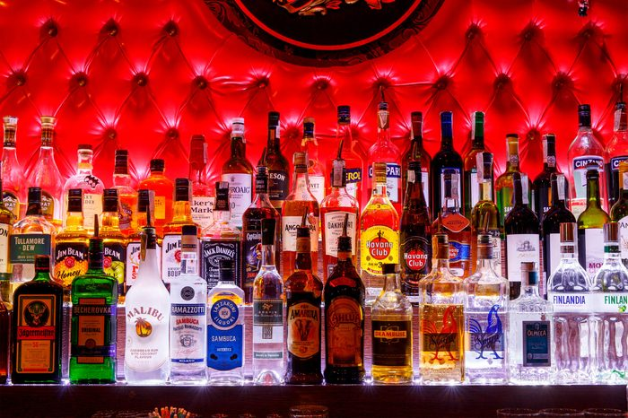 Alcohol bottles on a bar with a sexy quilted red background