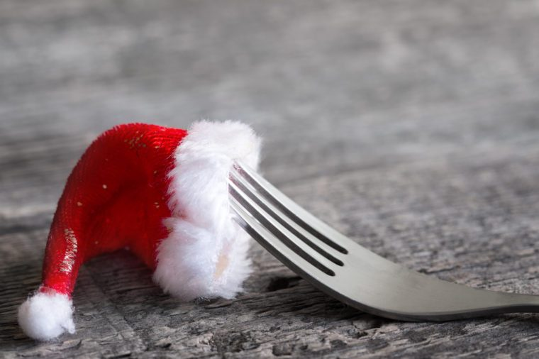 Christmas food menu abstract background with fork and santa claus hat on table