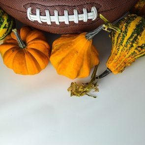 The ball for football with pumpkins on the white background. The picture is awesome for fall football game invitation card.
