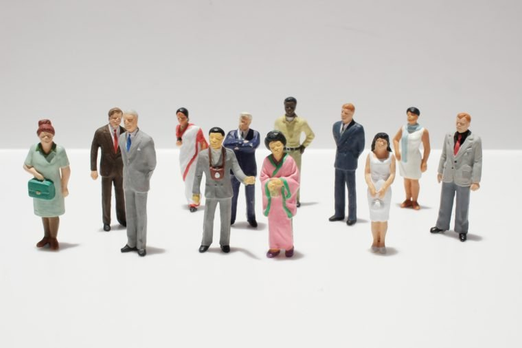 Miniature figures assembled on white and gray background