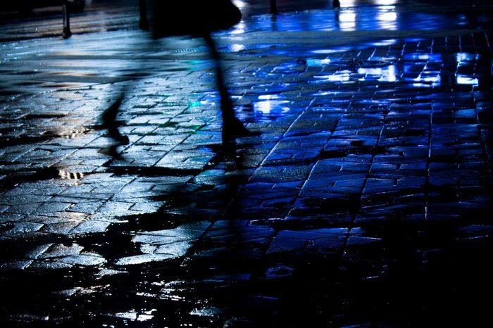Rainy city street reflections: Legs of a young woman walking in the night