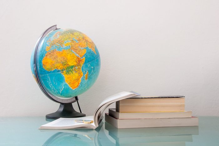 desk with a pile of books and school supplies like pencils and stationery and world map globe, back to school college university education concept, homework classroom study