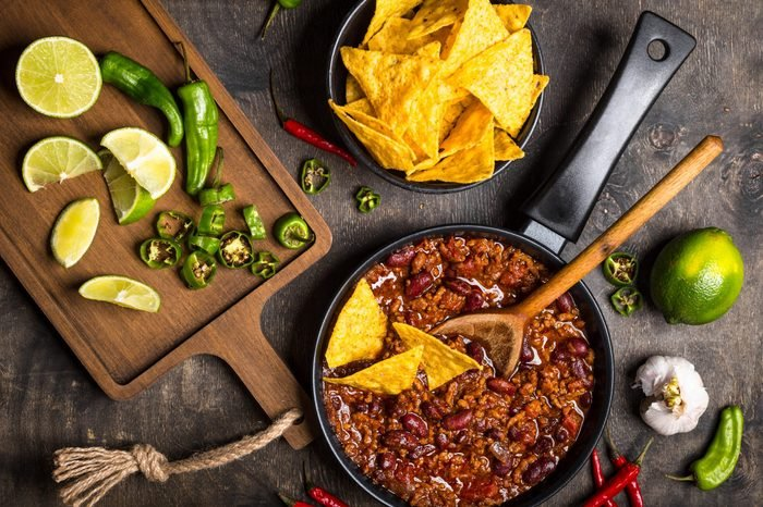 Chili con carne in frying pan on dark wooden background. Ingredients for making Chili con carne. Top view. Chili with meat, nachos, lime, hot pepper. Mexican/Texas traditional dish Chili con carne