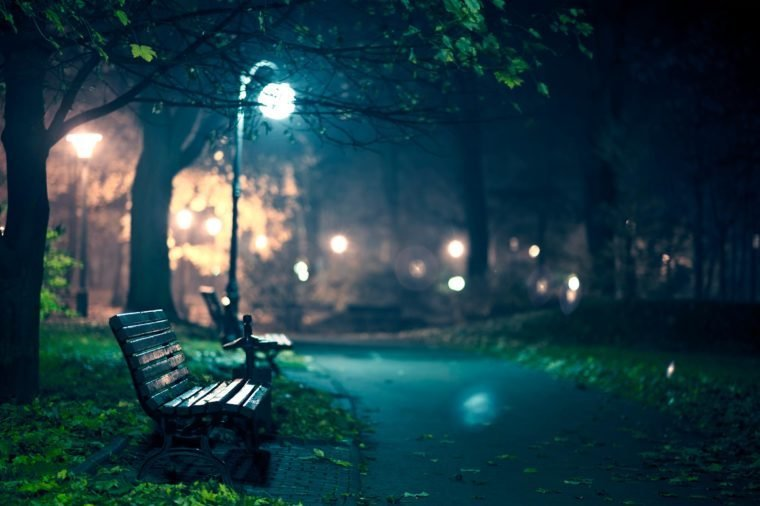 park benches lit by a street lamp at night