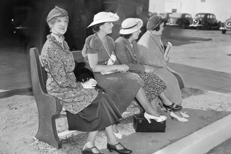 Four women sitting on a bench waiting for the bus
