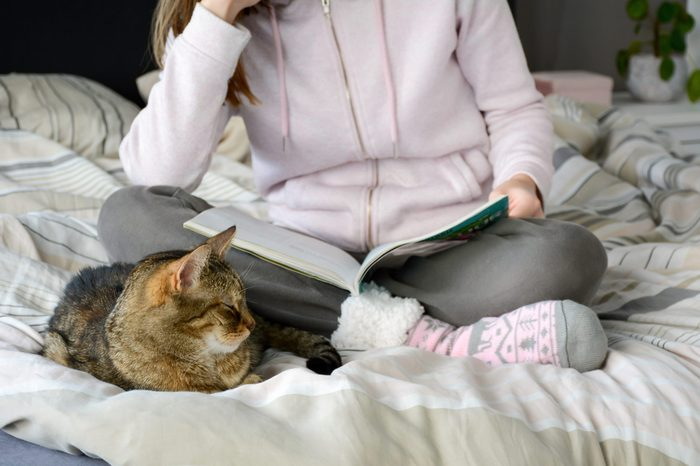 Young woman wearing warm comfortable winter sweater and socks reading a magazine on bed. Her cat is sleeping next to her. Cozy morning at home. Morning, leisure, relaxation, weekend concept.