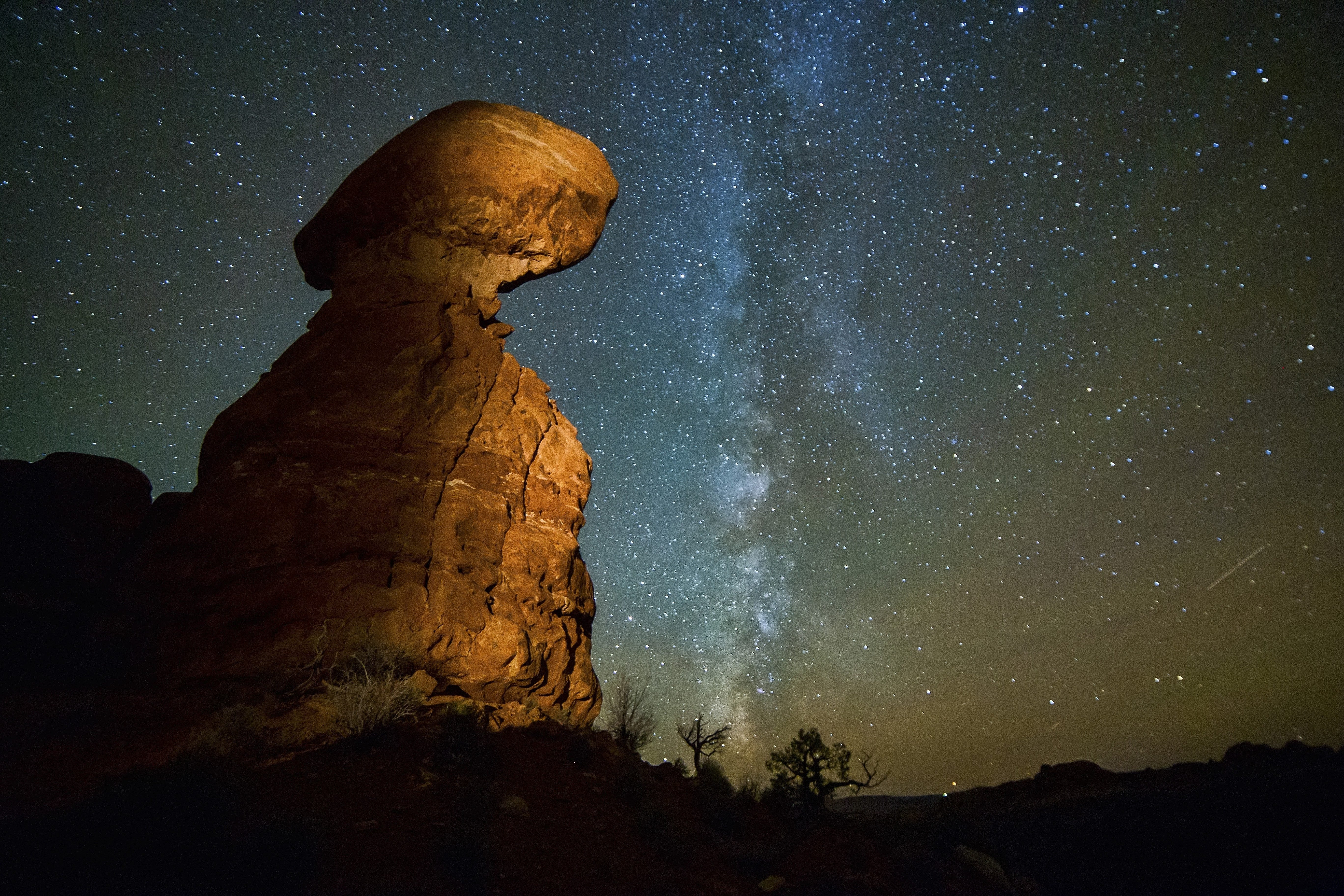 Night shot of Balanced Rock at Arches National Park in Utah, with the Milky Way visible in the dark sky.