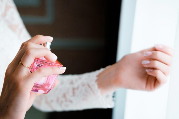 hands and perfume, beautiful gentle female hands, pink jar of perfume, lace sleeves