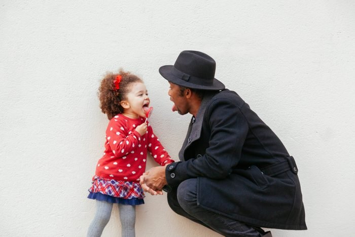 little girl licking a big candy with daddy