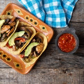 Mexican vegan tacos with avocado and mushrooms on wooden background