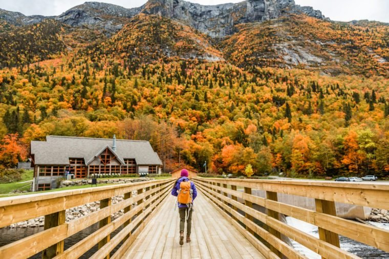Autumn nature hiker girl walking in national park in Quebec with backpack. Woman tourist going camping in forest. Canada travel hiking tourism at Hautes-Gorges-de-la-Riviere-Malbaie National Park.