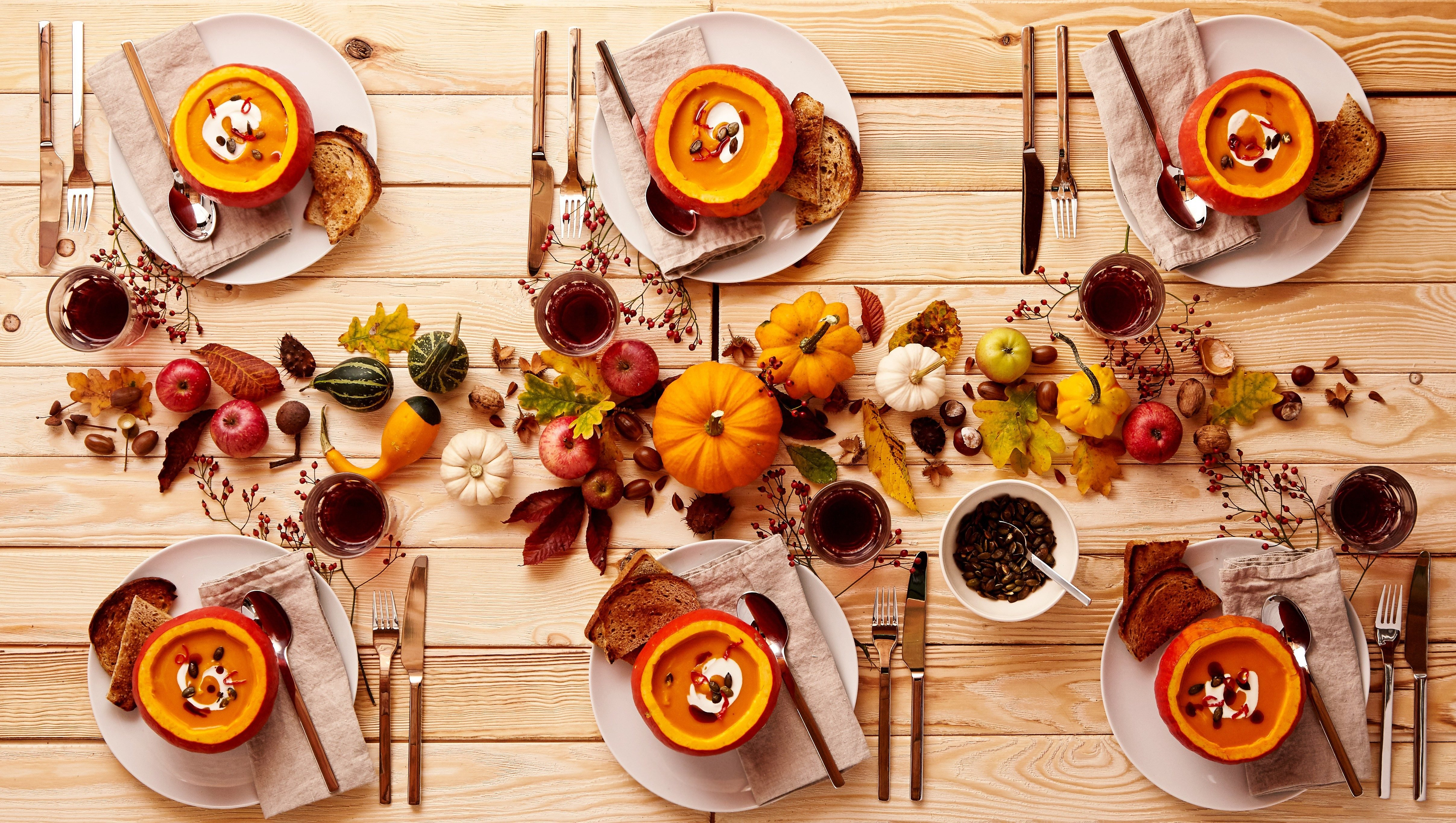 Top down view on place setting of pumpkin soup and cider on wooden table. Dinner or lunch for a party of six.
