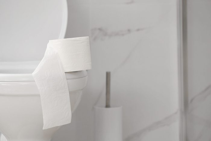 Paper roll on toilet bowl in bathroom