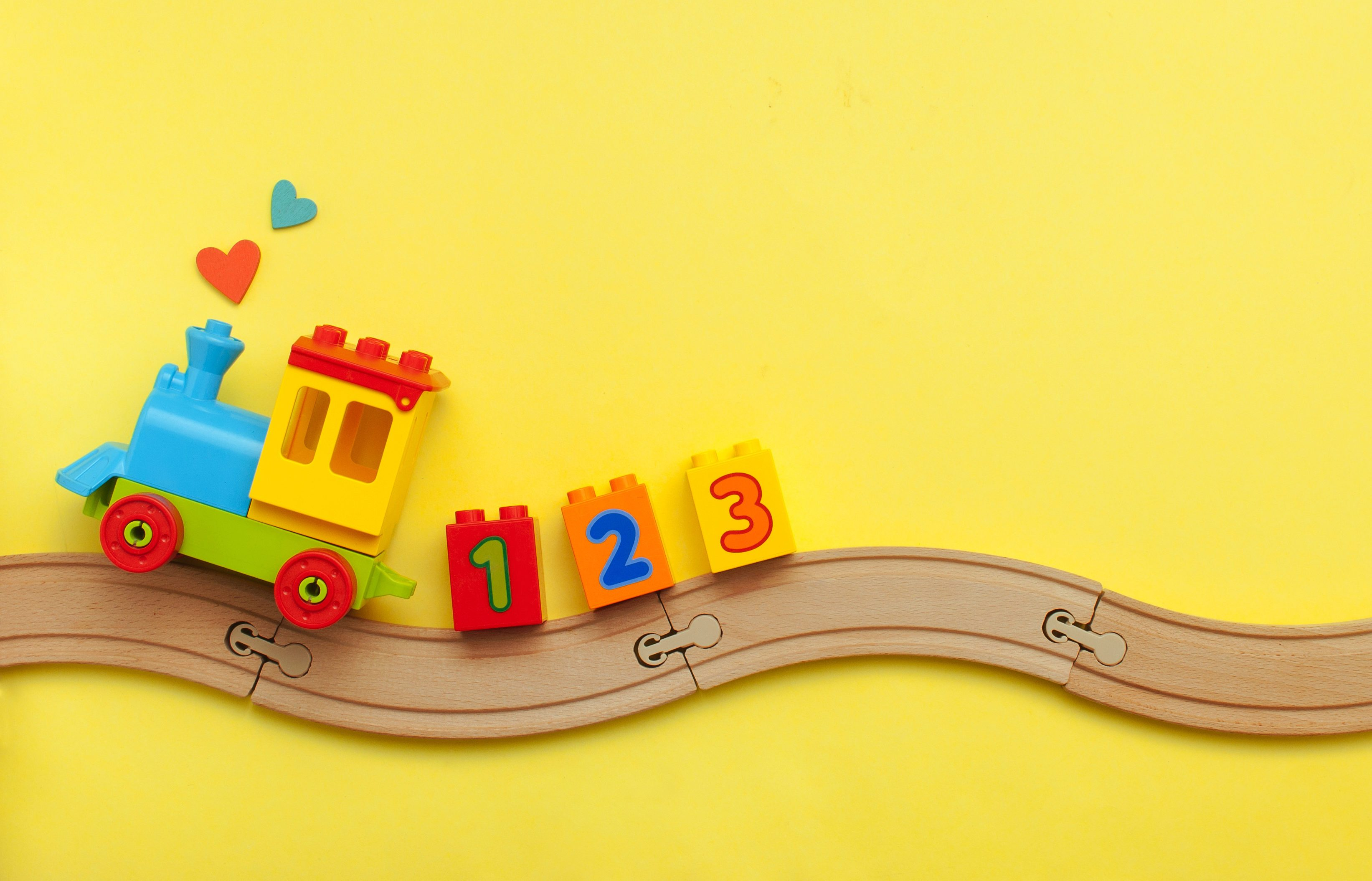 Toys background with copy space. Kids toy train with numbers on toy wooden railway on yellow background with blank space for text. Top view, flat lay.
