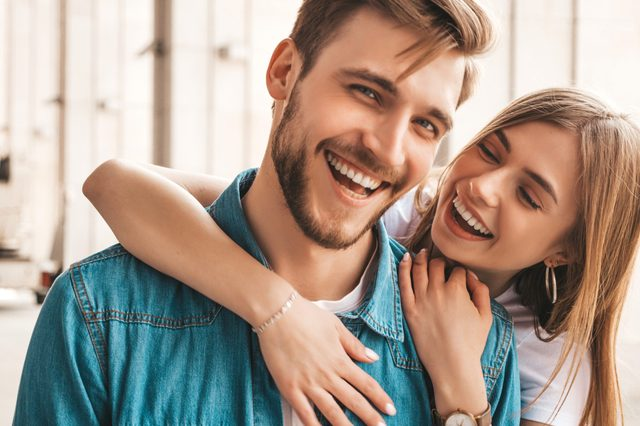 Portrait of smiling beautiful girl and her handsome boyfriend. Woman in casual summer jeans clothes. Happy cheerful family. Female having fun on the street background