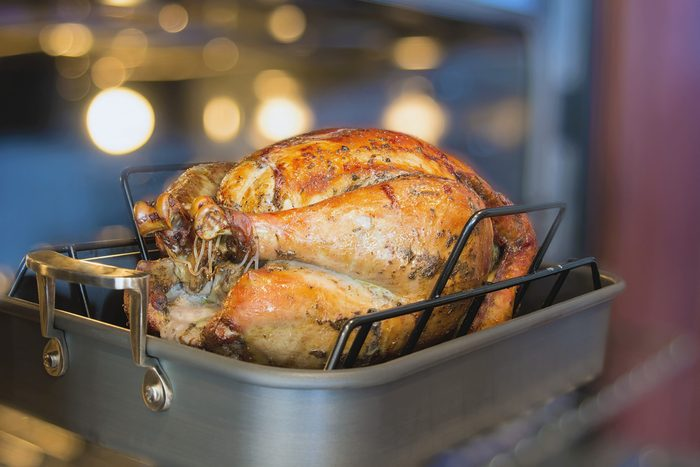 Turkey Cooked Brined and Seasoned with Spices in Roasting Pan for Thanksgiving Dinner with Blurred Oven Background